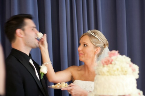 Bride shoving wedding cake into groom's nose