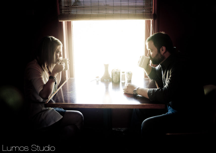A couple sips coffee during their engagement photos