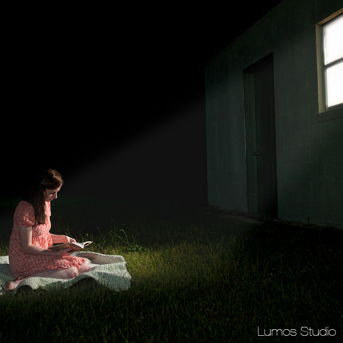 GIrl reads in a field by the light of a window
