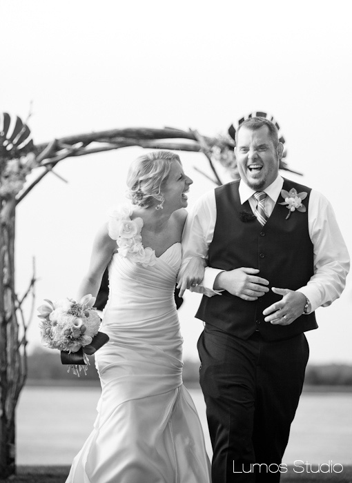 Bride and groom laugh as they walk down the aisle