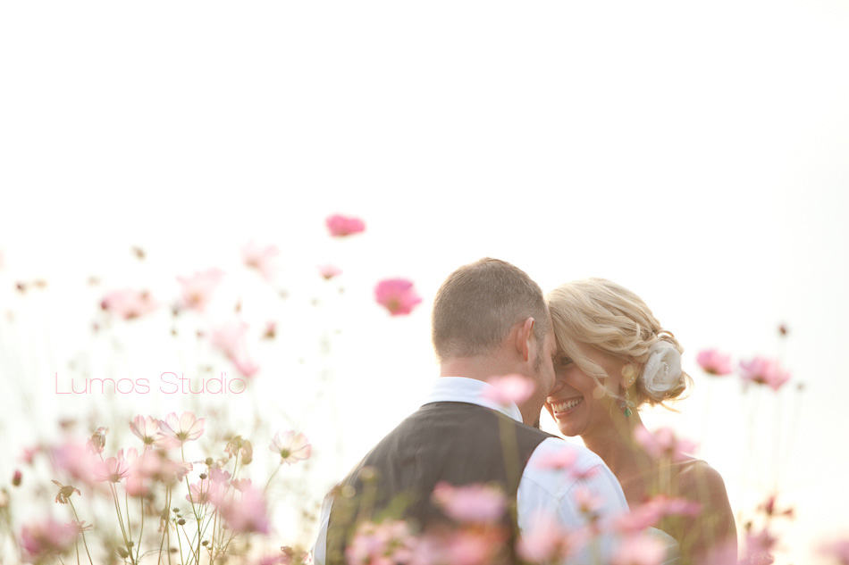 Bride and groom in a field of pink flowers