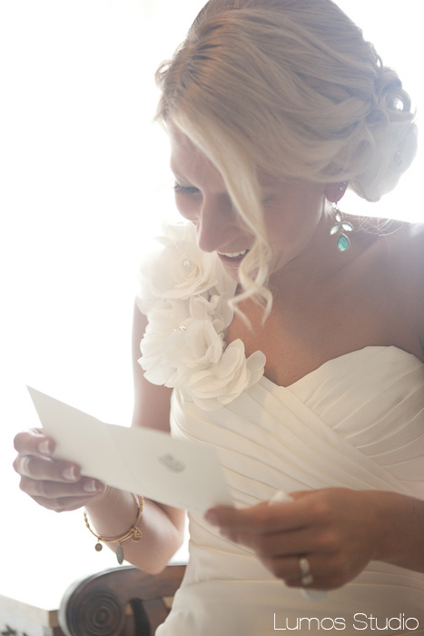 A bride smiles at a letter from her groom