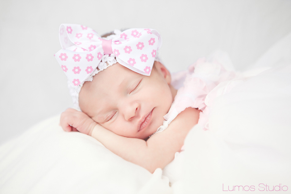 A sleepy baby girl wearing a pink bow