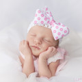 Newborn poses with her hands on her cheeks in Columbia, SC