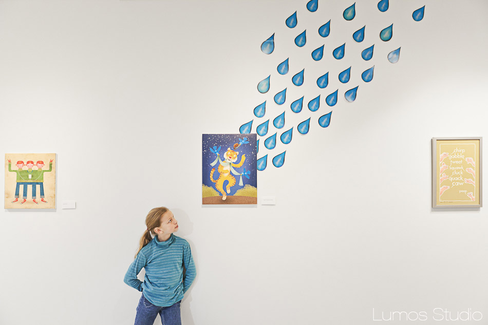 A little girl looks at an illustration by Brandon Reese at Richland Library