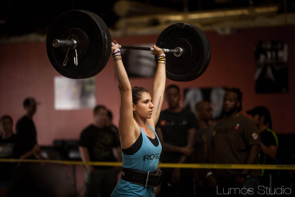 A woman doing a CrossFit WOD lifts a barbell over her head