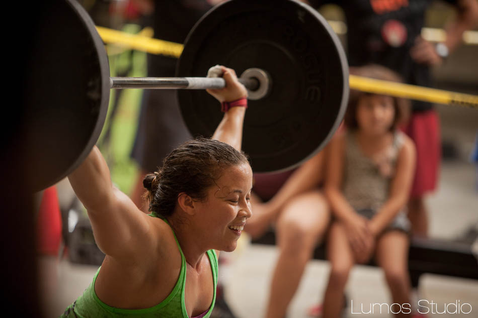 A female athlete smiles while performing overhead squats