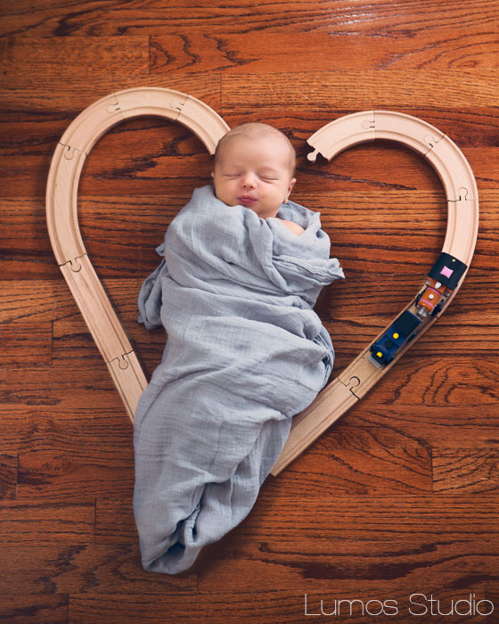 Newborn inside heart made of train tracks