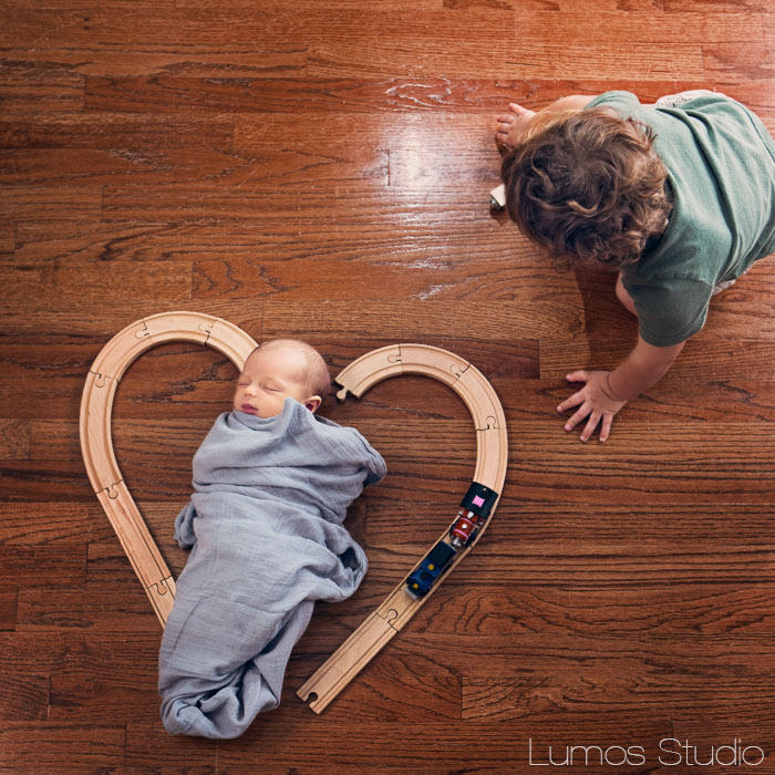 Baby inside heart made of train tracks while brother plays nearby
